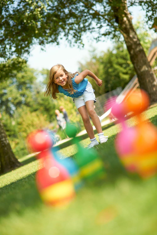 Sechsjähriges Mädchen spielt stehend draußen mi bunten Kunstoffkugeln