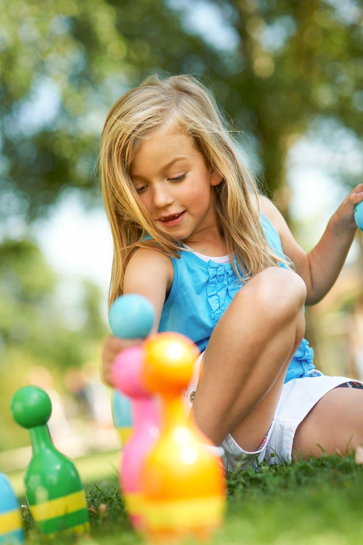 Portrait eines jungen Mädchen das in der Natur mit bunten Kunstoffkugeln spielt