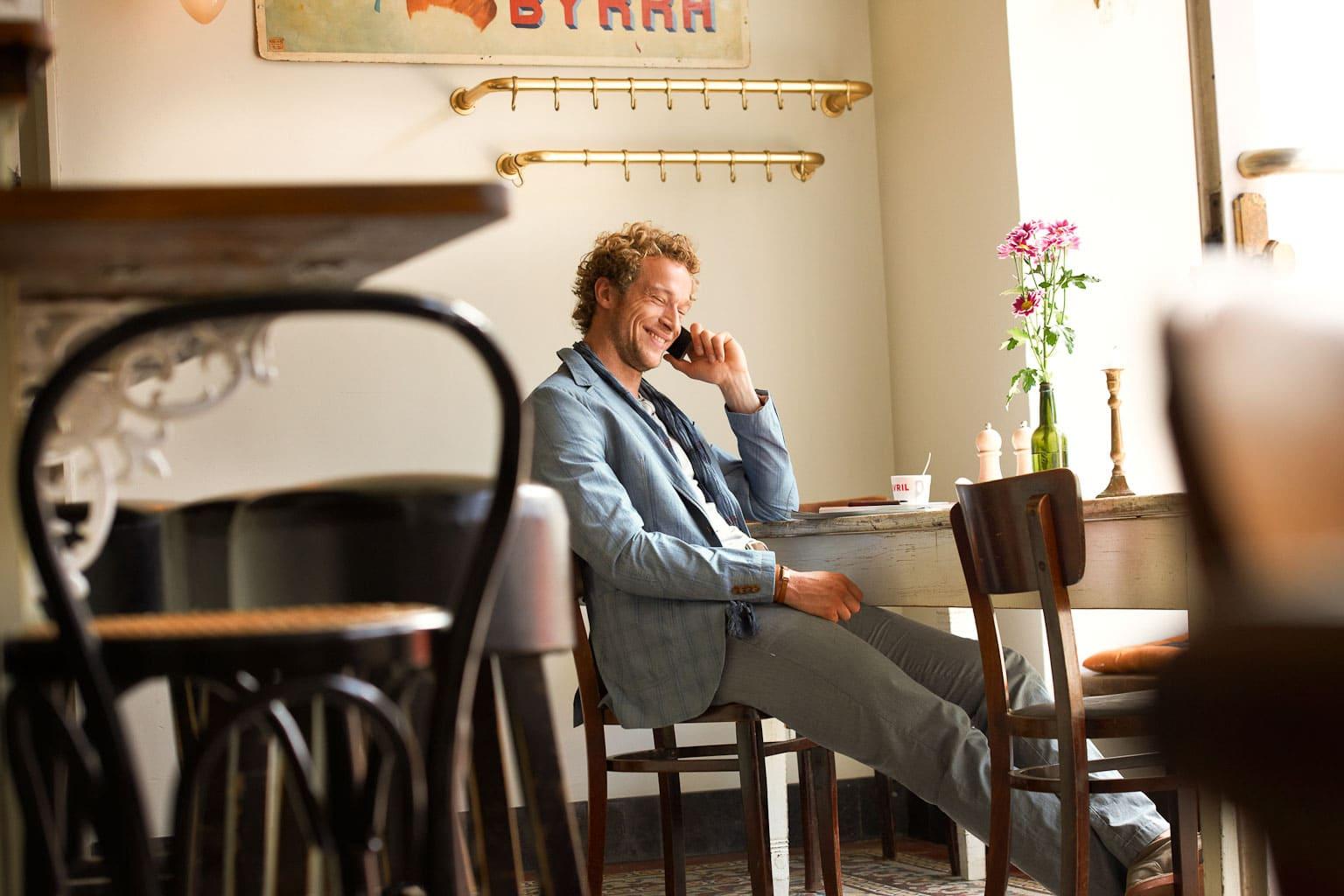 Portrait eines Mannes der in einem hellen Lokal auf einem Stuhl sitzend genüßlich telefoniert
