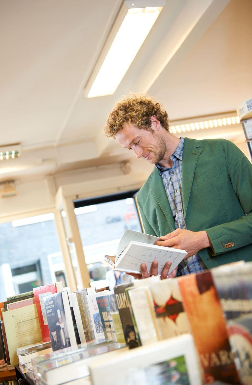 Portrait eines Mannes in hellgrünem Jacket in einer Buchhandlung, der in einem Buch blättert