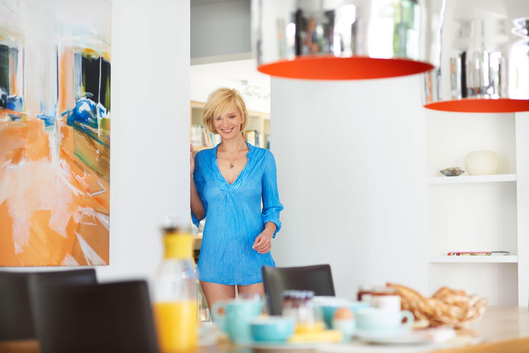Portrait einer gerade aufgestandenen Frau, die glücklich an den gedeckten Frühstückstisch kommt