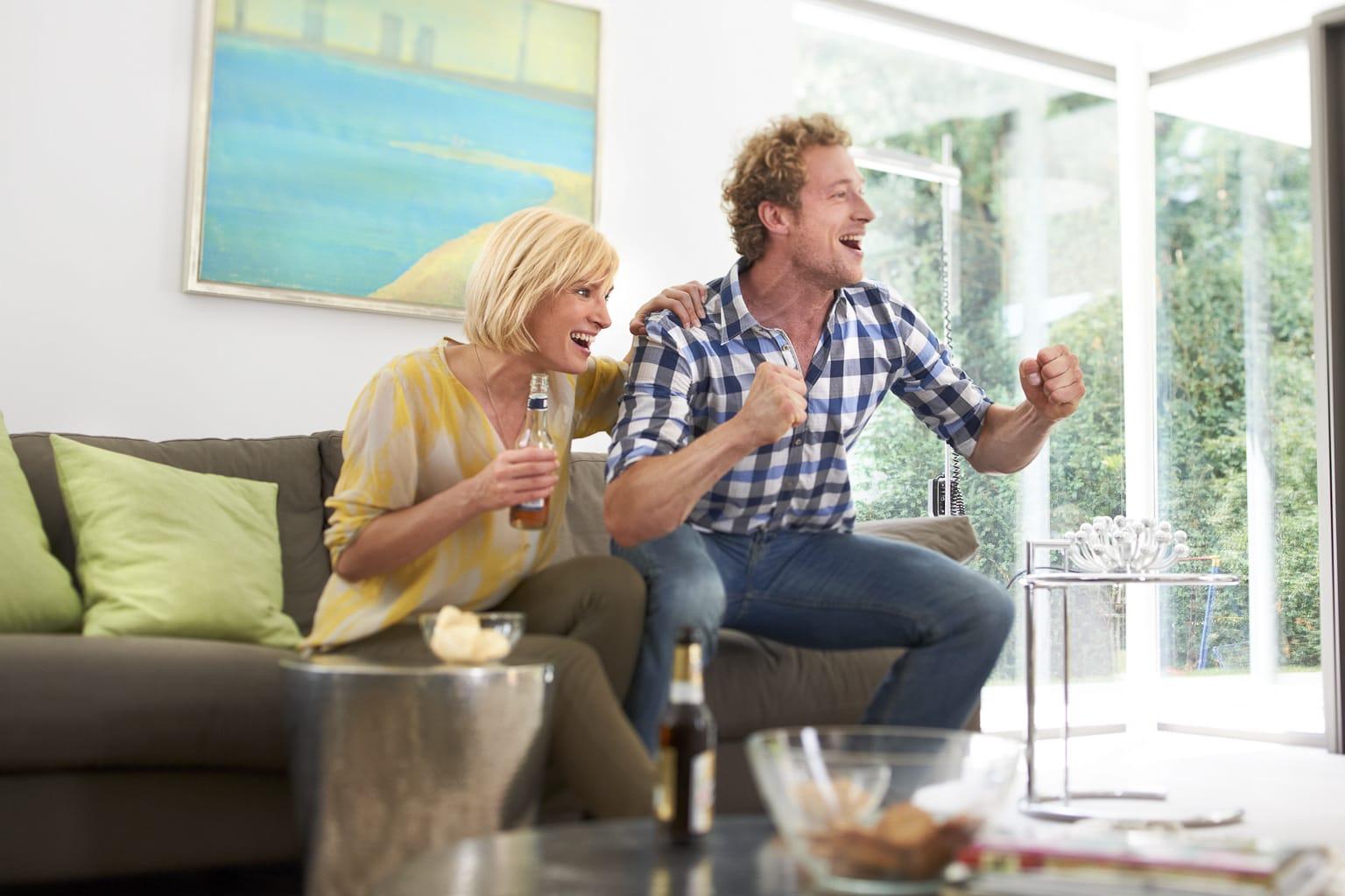 Portrait eines Paares vor dem imaginären Fernsehgerät jubelnd in dem Moment, wo das Tor fällt