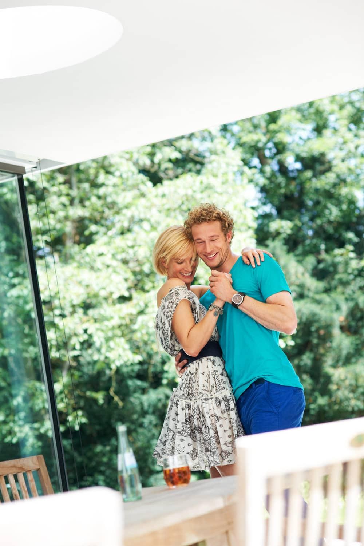 Portrait eines tanzenden jungen Paares auf einer Terrasse vor grünem Hintergrund