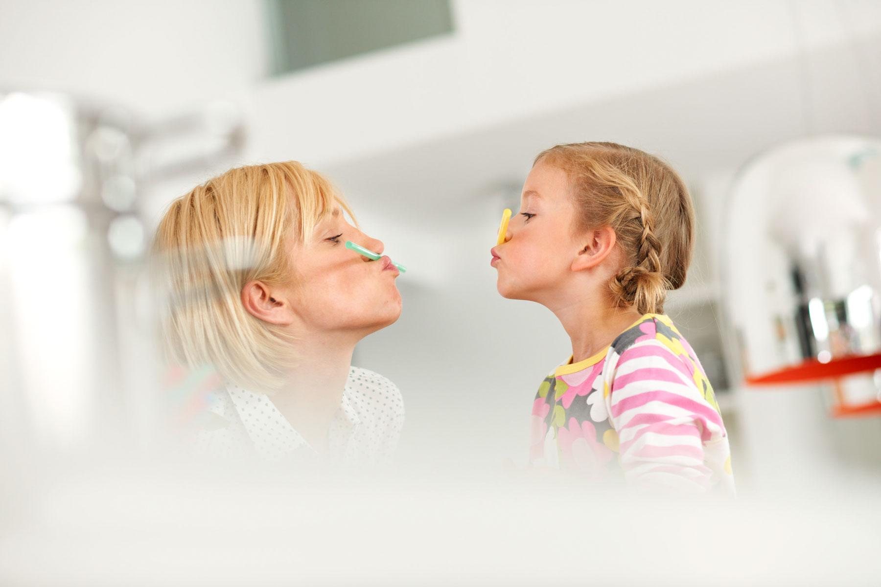 Foto von Mutter und Tochter, die je einen bunten Strohhalm zwischen ihrem Mund und Nase halten