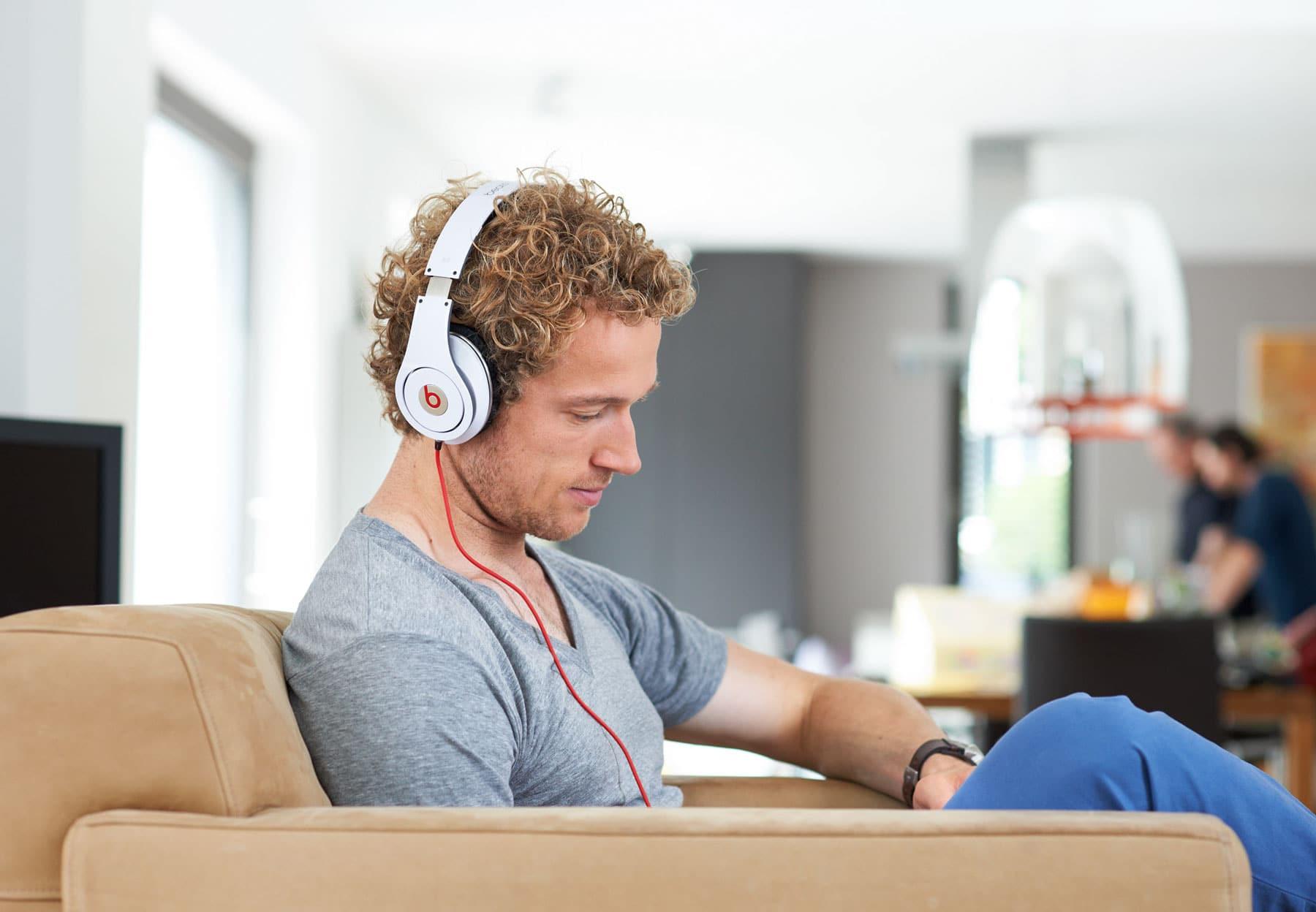 Portrait einer junger Mann mit weißem Kopfhörer in modernem Ambiente