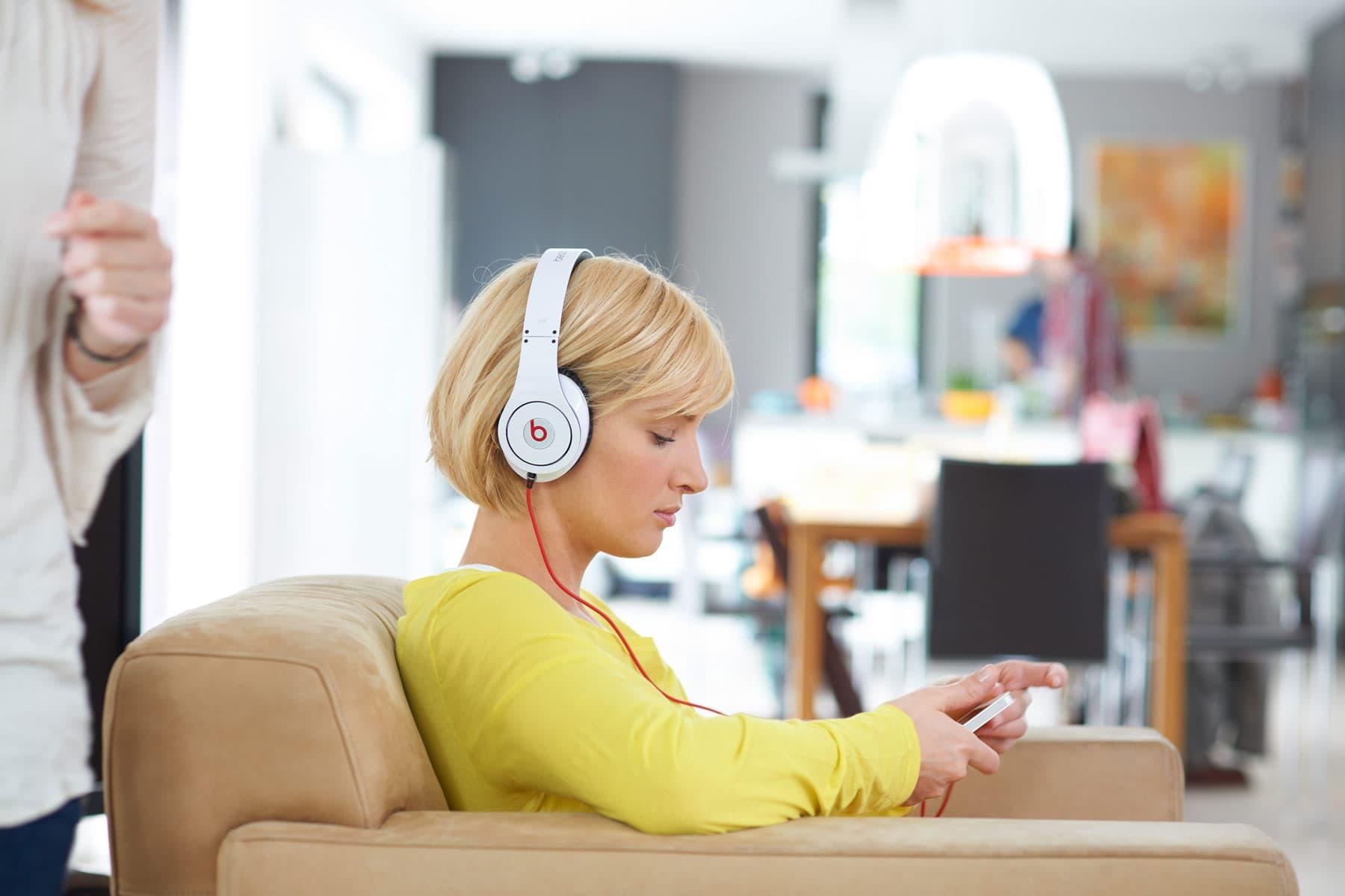 Portrait einer jungen Frau mit weißem Kopfhörer und ihrem Mobilpone in modernem Ambiente