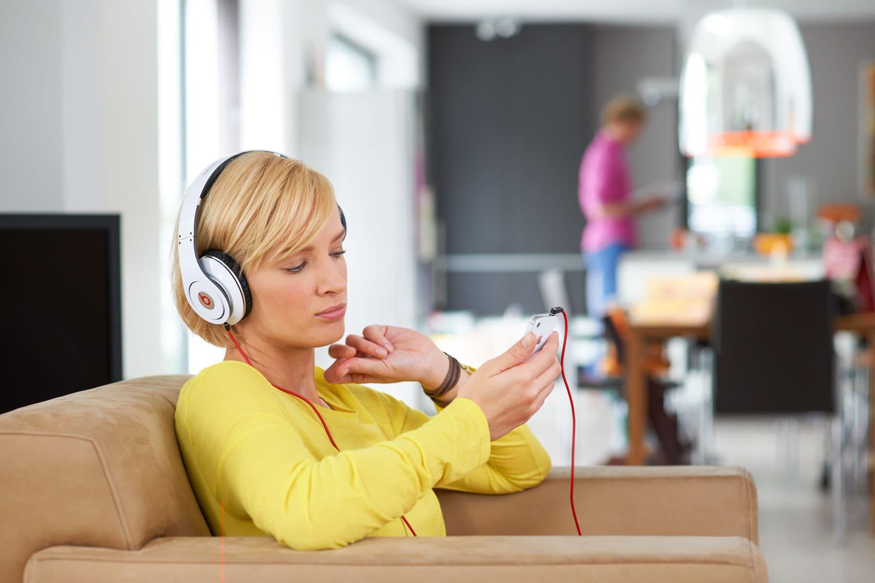 Portrait einer jungen Frau mit weißem Kopfhörer und ihrem Mobilpone in anspruchsvollem Ambiente