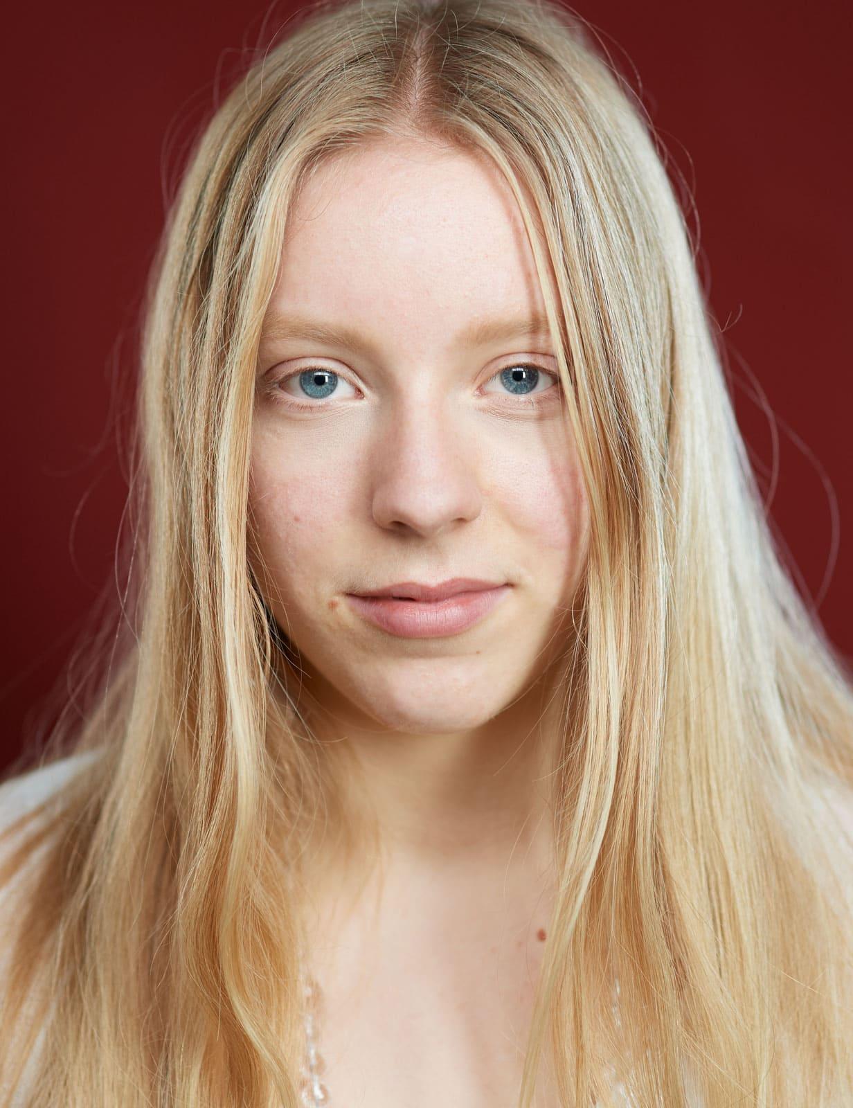 Portrait einer jungen Frau die sehr tiefblickend den Betrachter fixiert