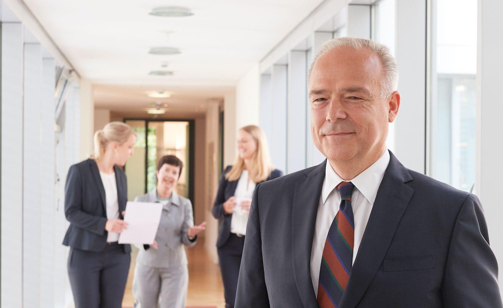 Portrait eines schmunzelnden Rechtsanwaltes in seiner Kanzlei
