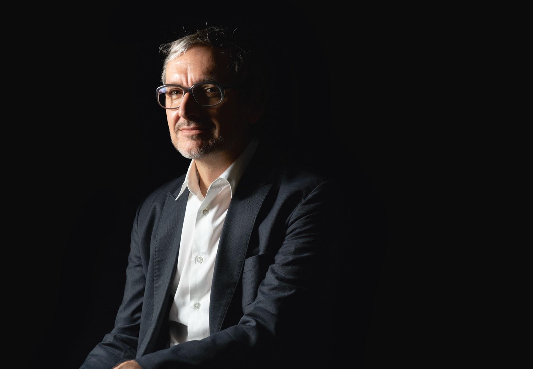 Portrait eines Architekten mit kräftiger Hornbrille vor Schwarz
