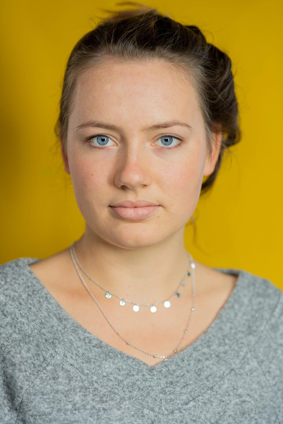 Portrait von einer schönen Frau vor gelben Hintergrund