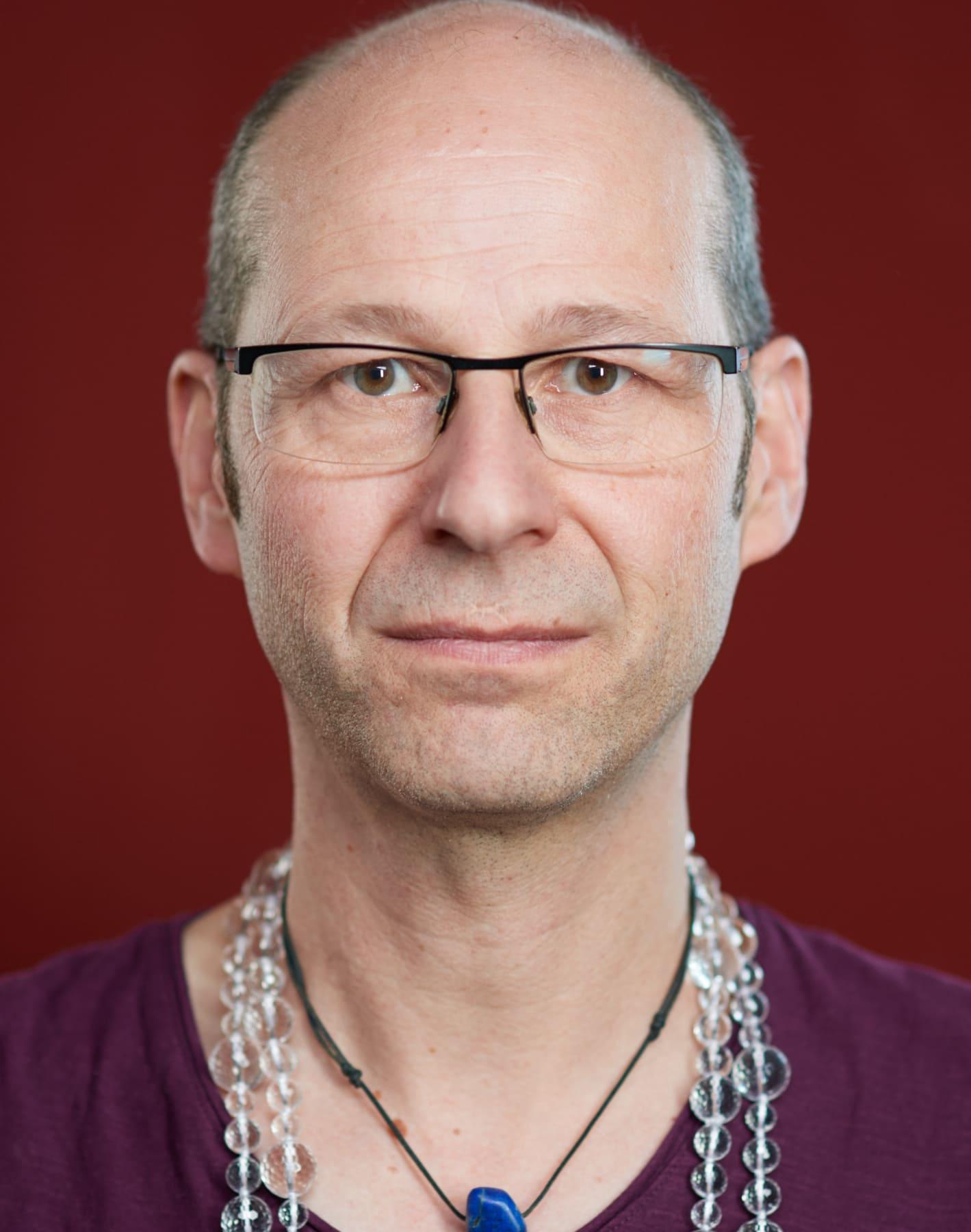Portrait eine Mann mit Brille vor rotem Hintergrund