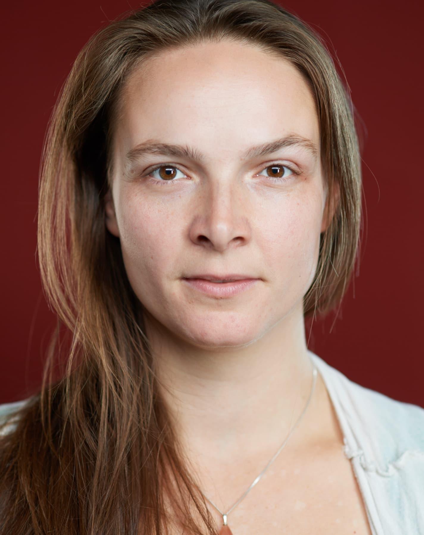 Portrait von einer entschlossenen Frau vor rotem Hintergrund