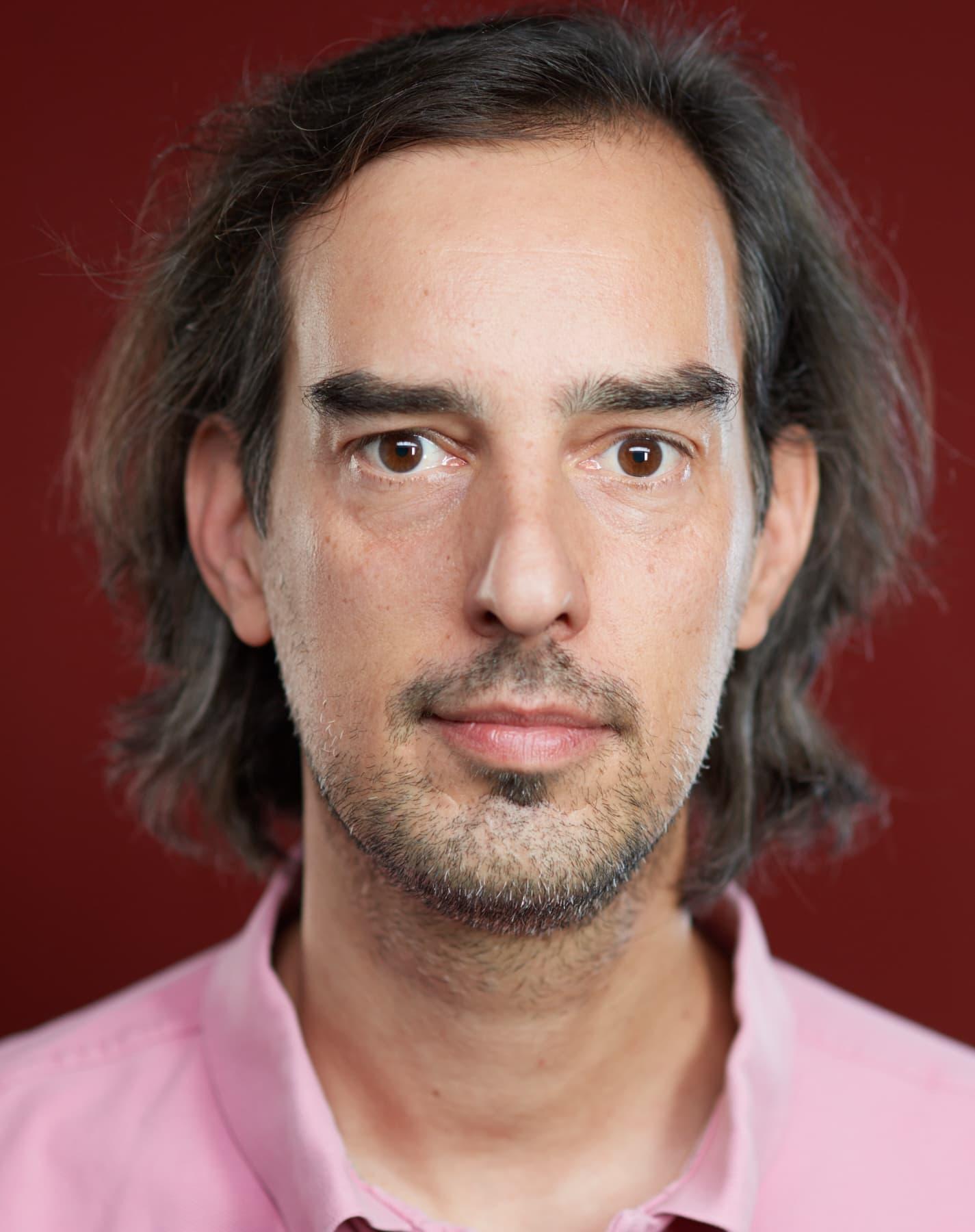 Portrait von eines Mannes mit dreitagebart vor rotem Hintergrund