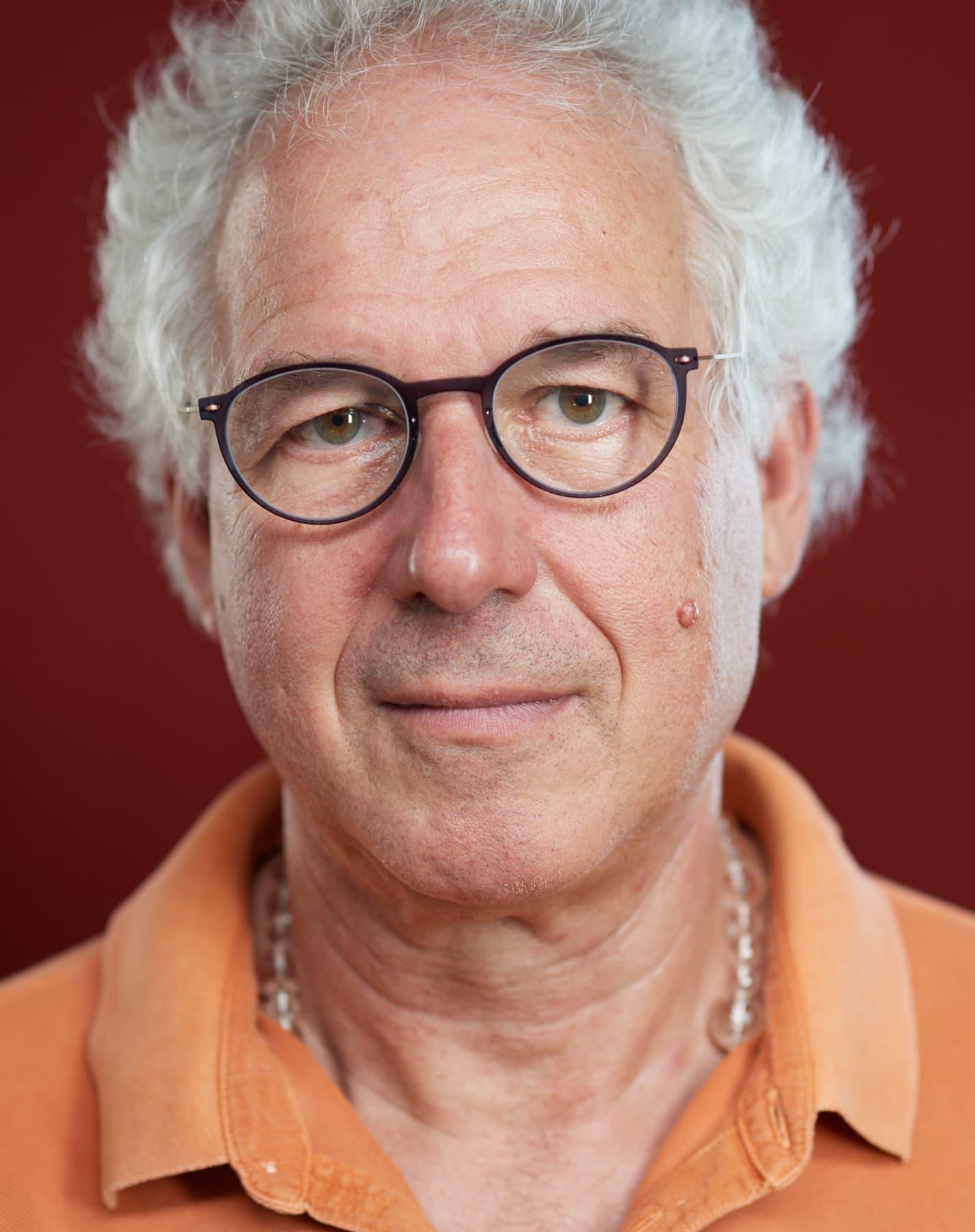 Portrait von eines Mannes mit grauem Haar vor rotem Hintergrund