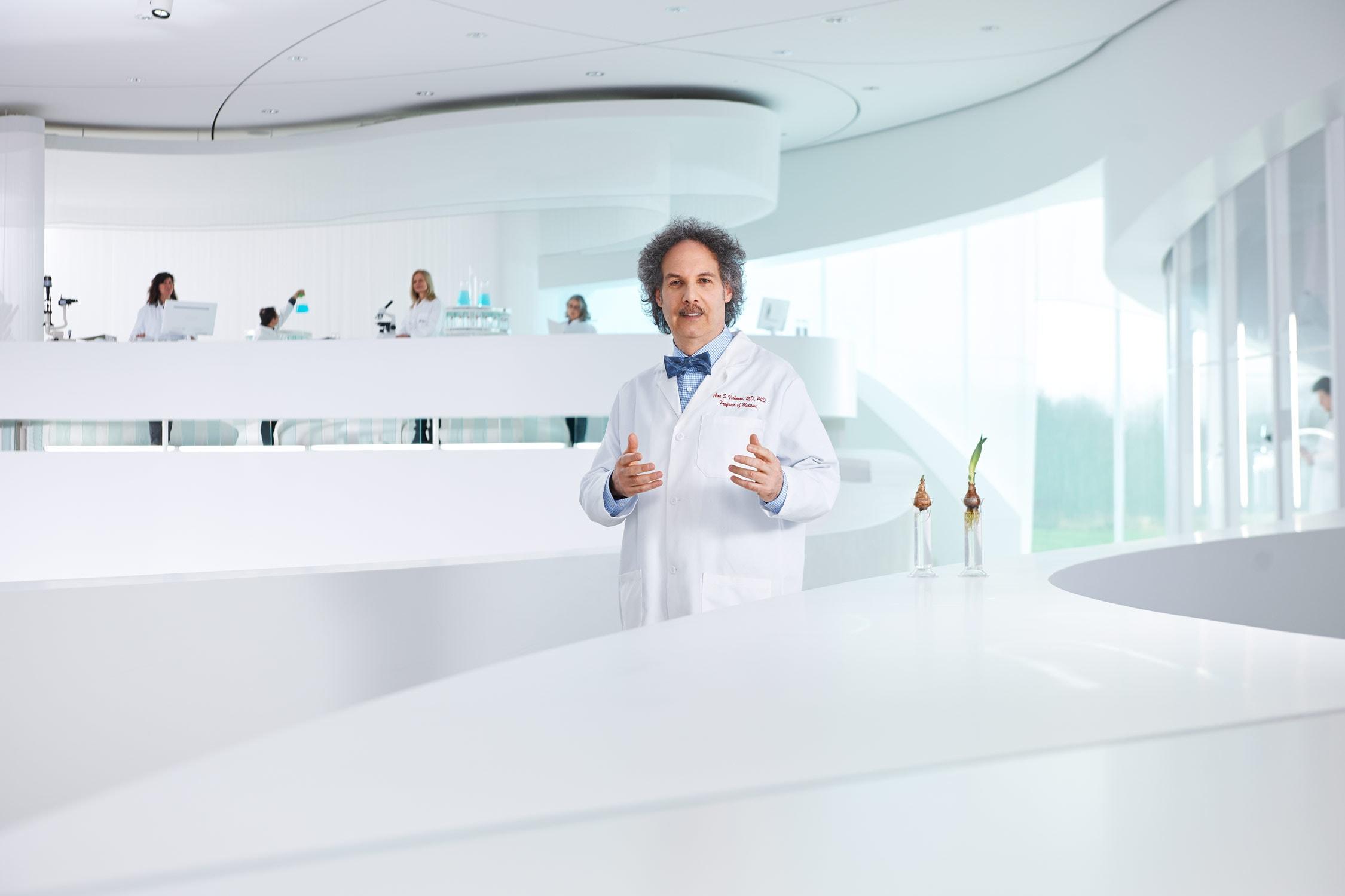 Portrait von einem Forschungsprofessor in eine großen, hellen Labor mit Mitarbeitern im Hintergrund
