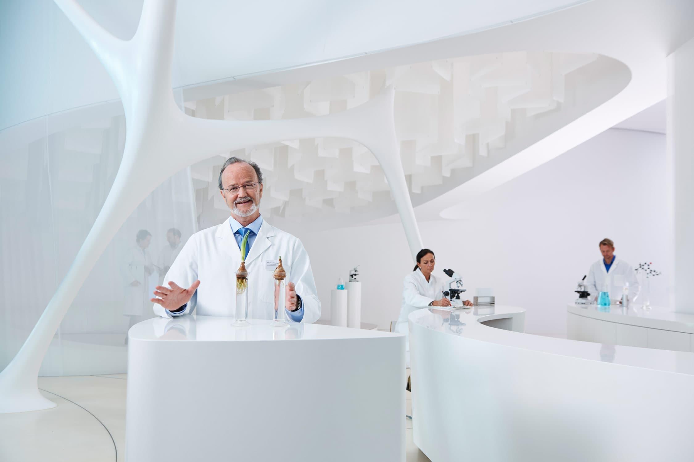 Portrait von einem Forschungsprofessor mit Mitarbeiter im Hintergrund in weißem Labor