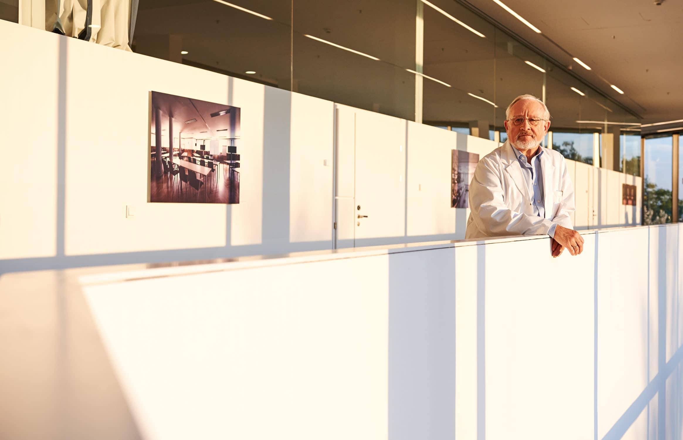 Portrait von einem Forschungsprofessor der sich im Sonnenlicht auf der Brüstung aufstützt