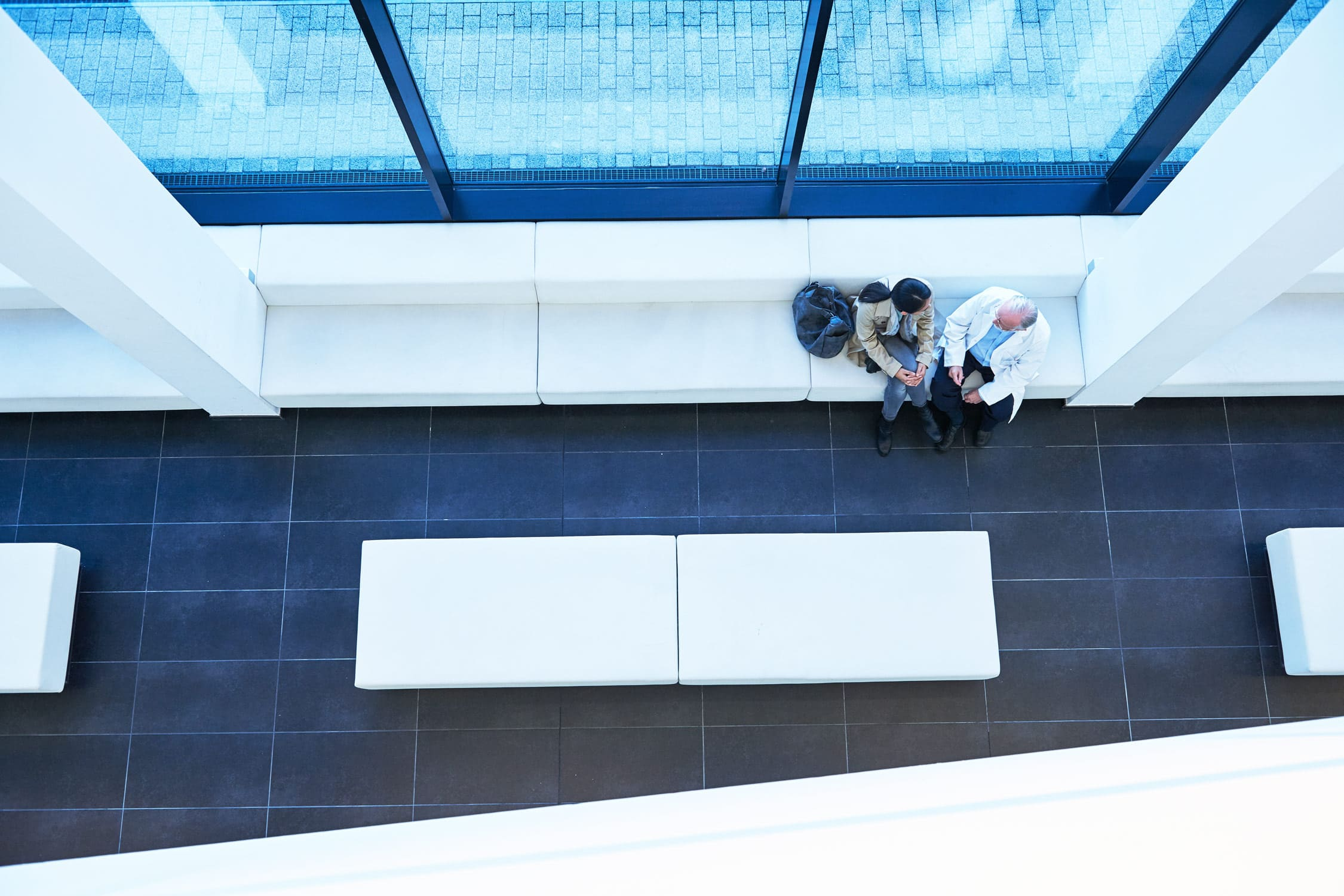 Blick von oben auf Fenstersitzbank auf der sich zwei Menschen unterhalten