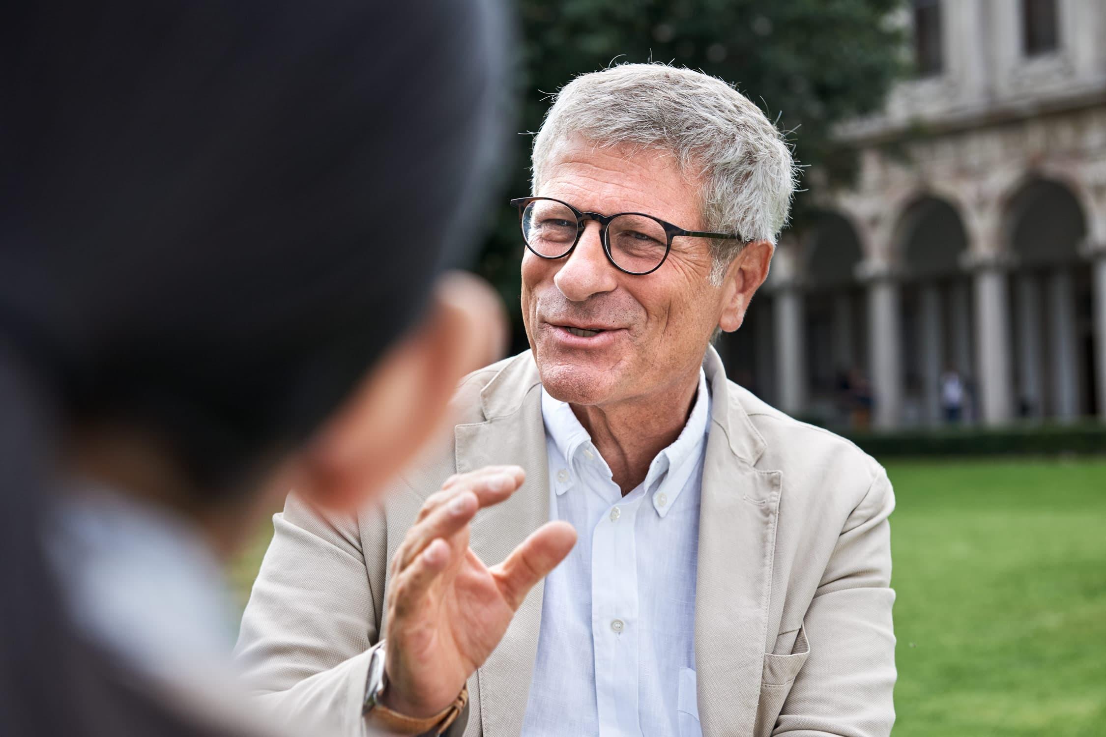Portrait von einem Forschungsprofessor mit unscharfer Interviewpartnerin im Vordergrund