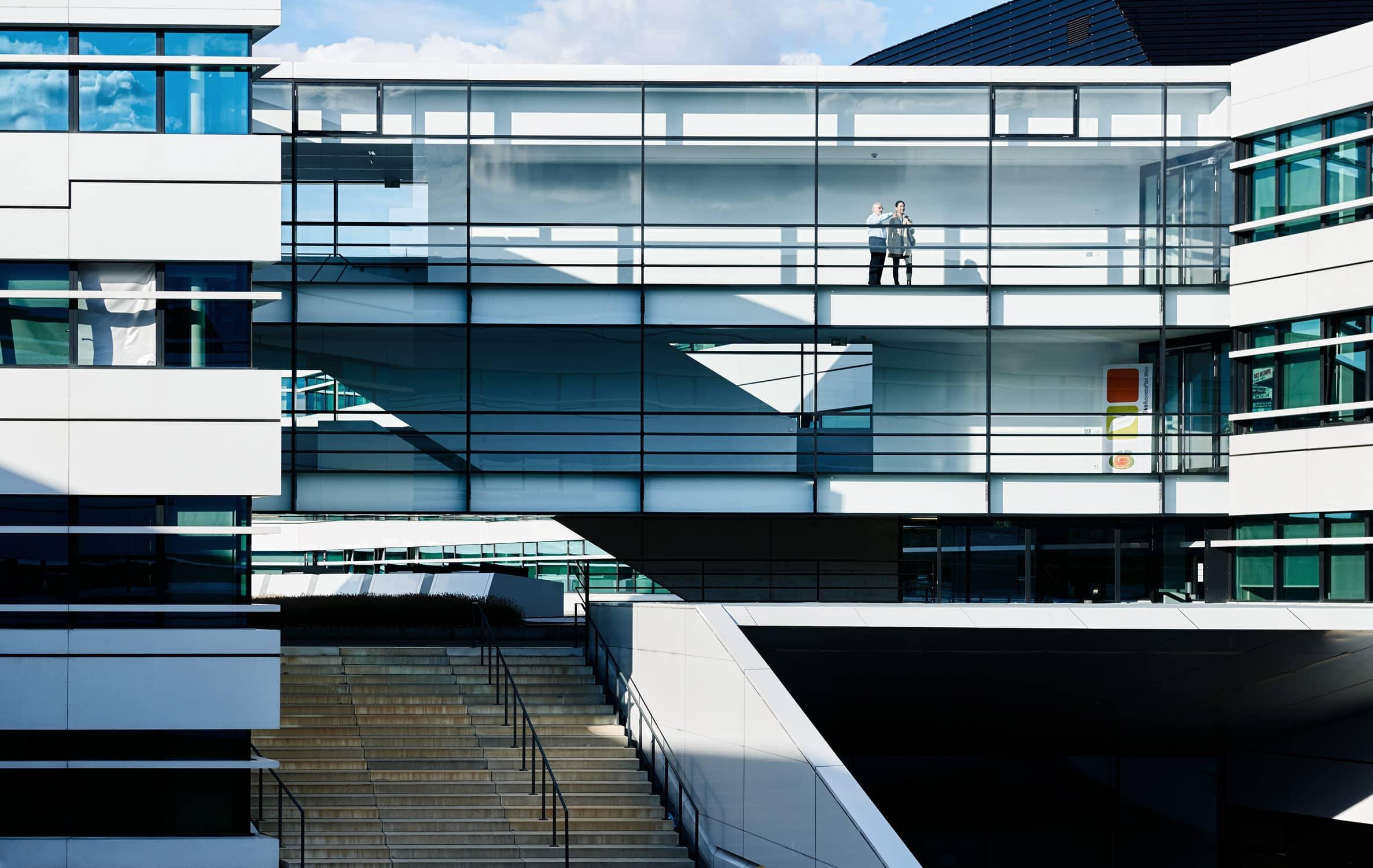 Modernes Universitätsgebäude von außen mit in der Ferne stehenden Menschen