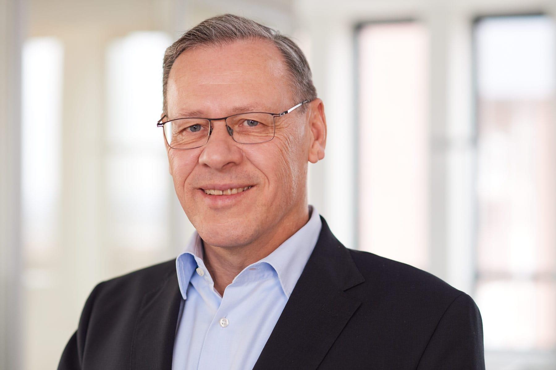 Portrait eines entspannten Geschäftsführers im grauem Sacko vor unscharfem Hintergrund