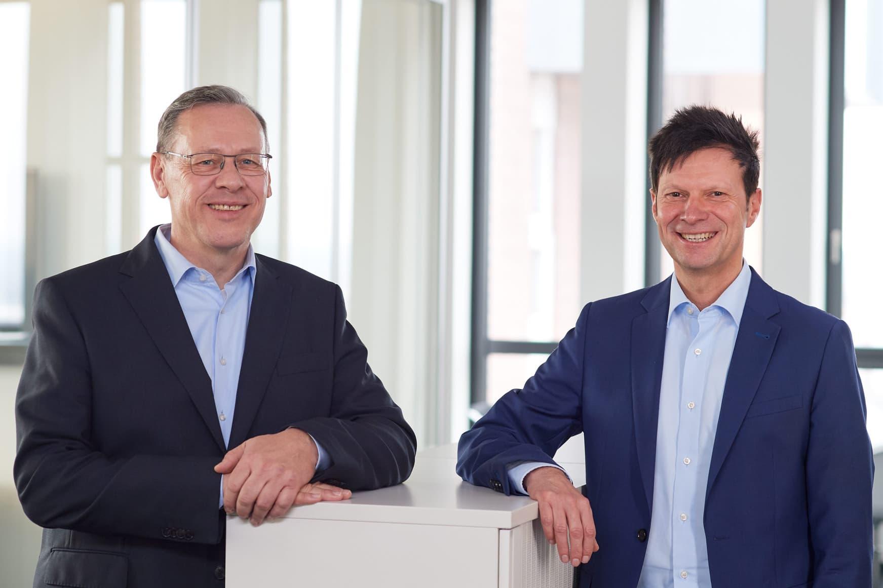 Freudiges Portrait zweier Geschäftsführer in ihren Büroräumen