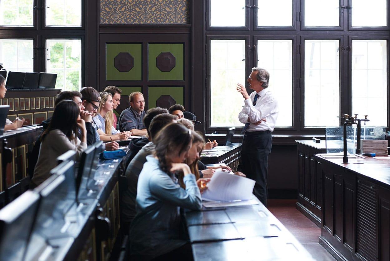 Portrait von einem Professor im alten Hörsaa vor seinen Studentenl