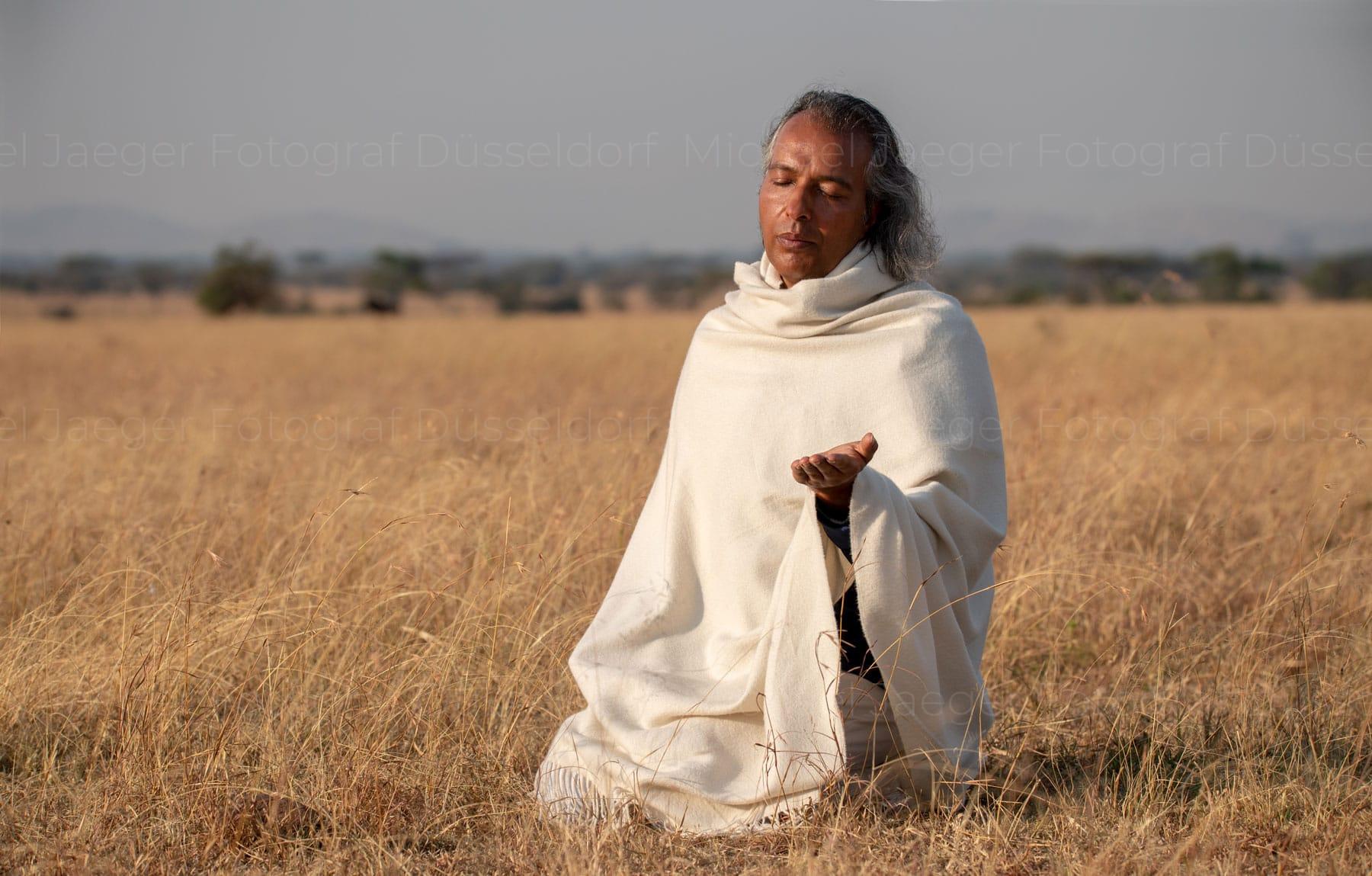 In Hingabe sitzender Mann segnet die Serengeti