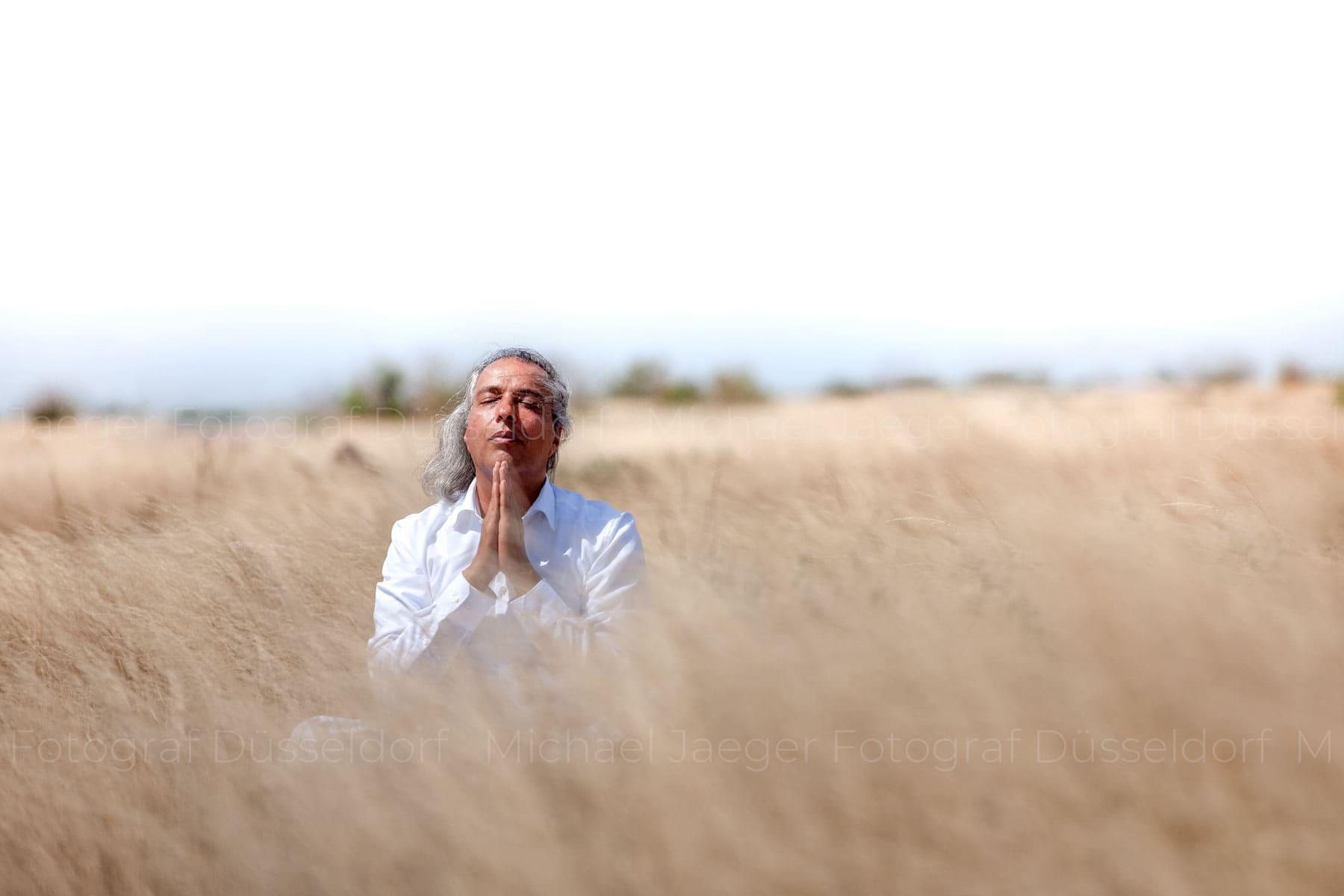 Meditierender Mann sitzend im hohen Gras der Serengeti