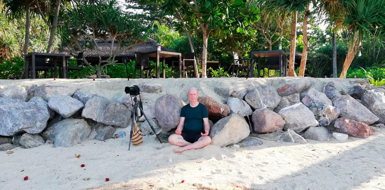 meditierender Fotograf am Strand