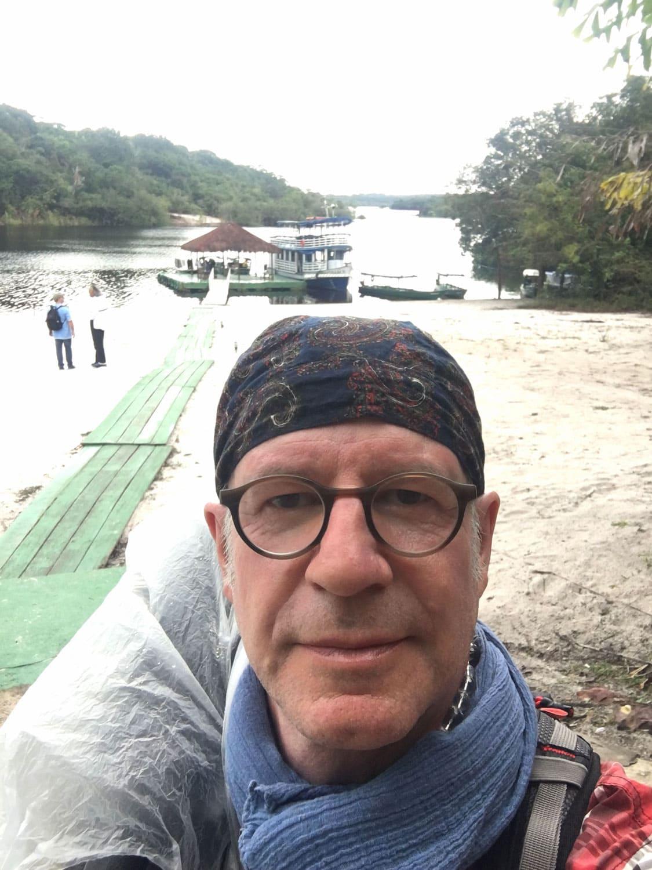 Selbstportrait eines Mannes mit Kopftuch an einem langen Bootssteg