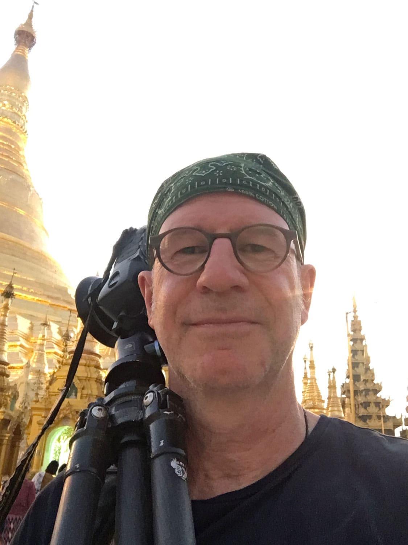Mann mit geschulterter Kamera auf Stativ schaut vor einem Tempel in die Kamera