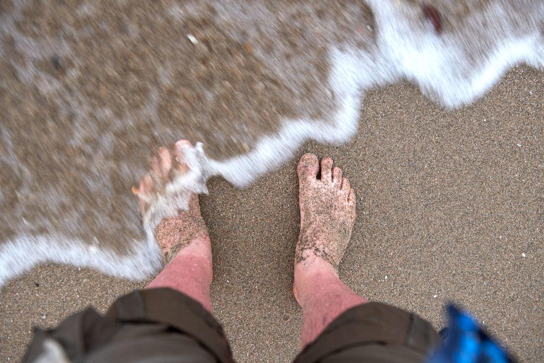 Jaeger steht mit rotverbraten Schienbeinen und seinen Füssen im Wasser am Strand