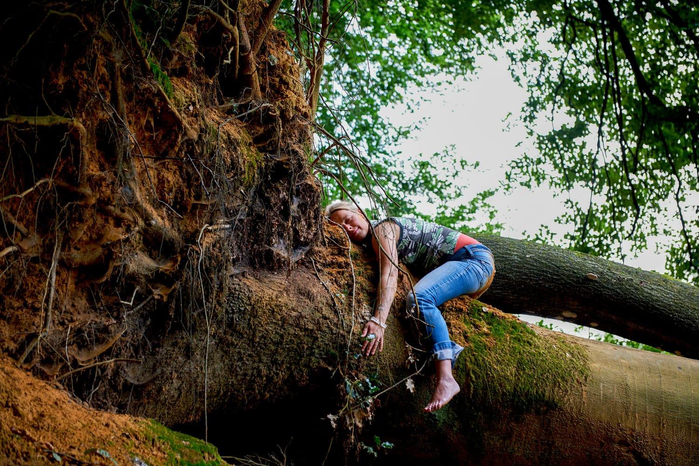 Frau liegt in völliger Hingabe auf einem entwurzelten Baum